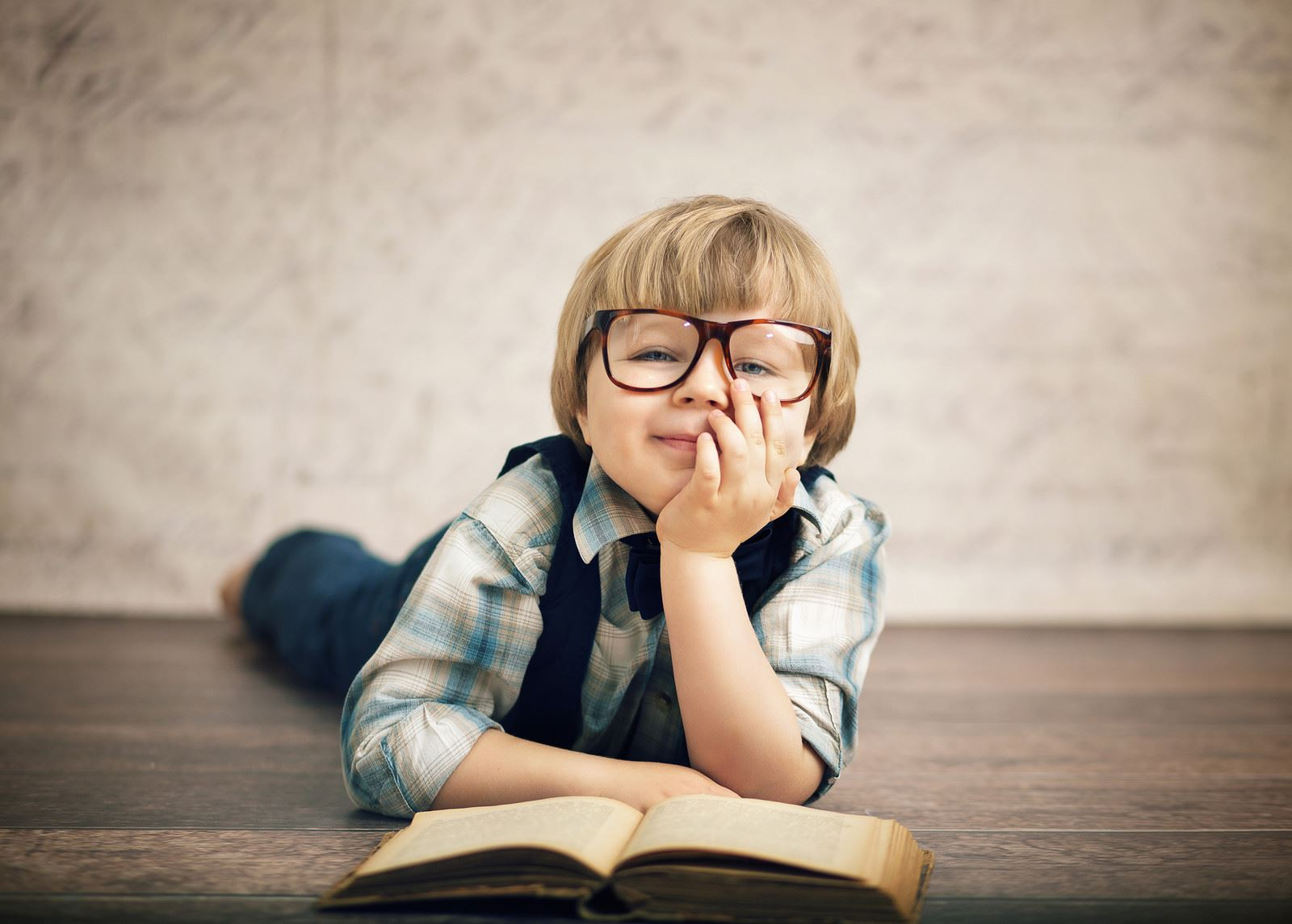 young boy with glasses laying on the floor reading a book